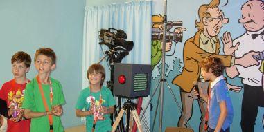 Kind leest in de nieuwskamer een nieuwsbericht voor uit een Suske en Wiske - verhaal.